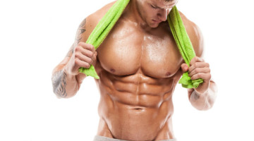 male with shirt off towel around neck displaying six pack abs