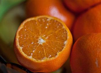 A cut open half of a juicy orange.