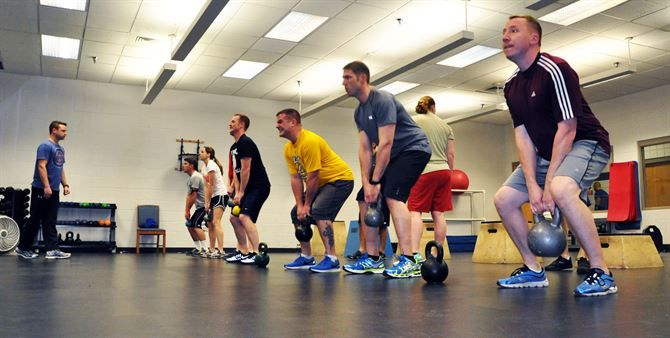Group in a room doing kettle bell exercises